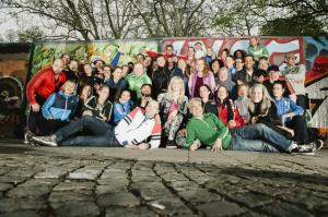 Klubbkören bestående av 30 personer poserar tillsammans framför en mur.